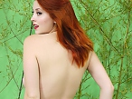 Busty redhead loses her clothes in jungle
