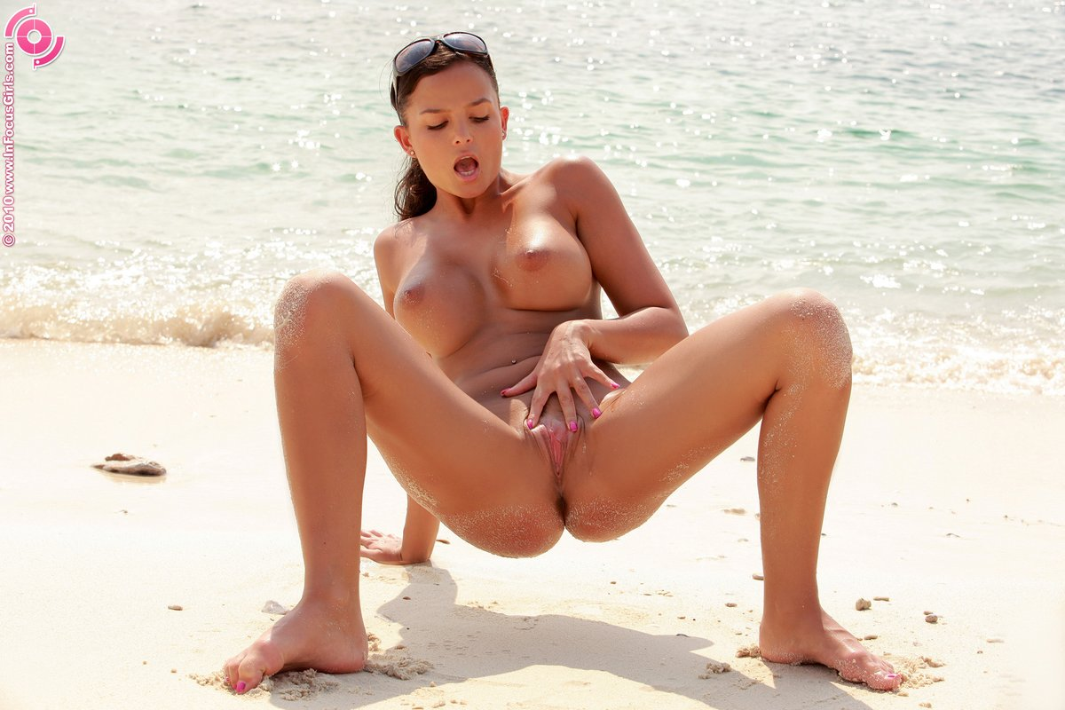 The heat of the sun warms up the nude body of this hot babe as she fingers herself in the sand