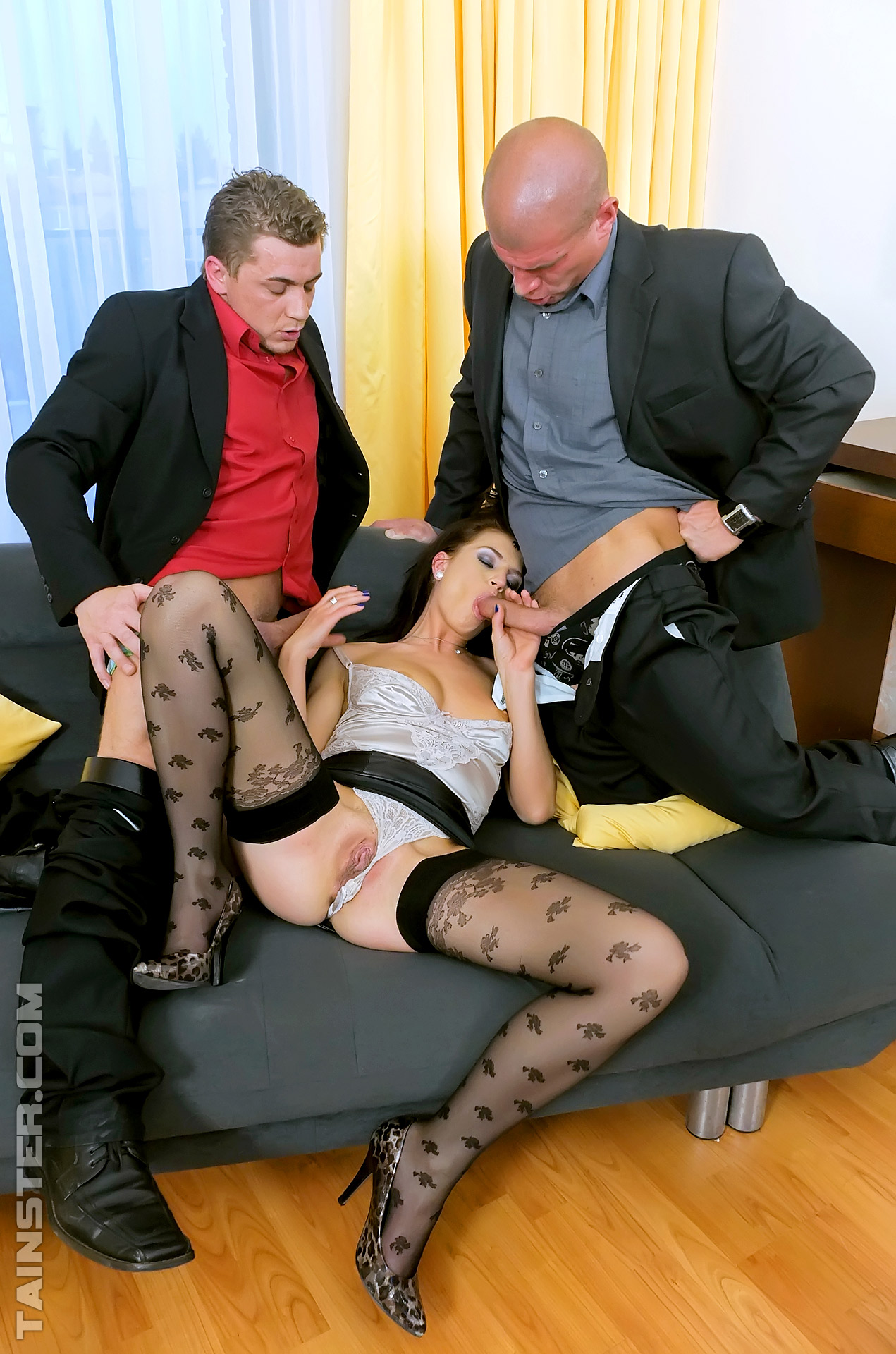 Fully clothed brunette takes on two cocks