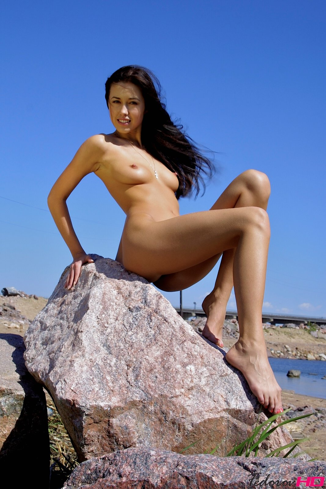 Bare skin against a blue sky shows the saucy exhibitionist side to this brunette posing nude