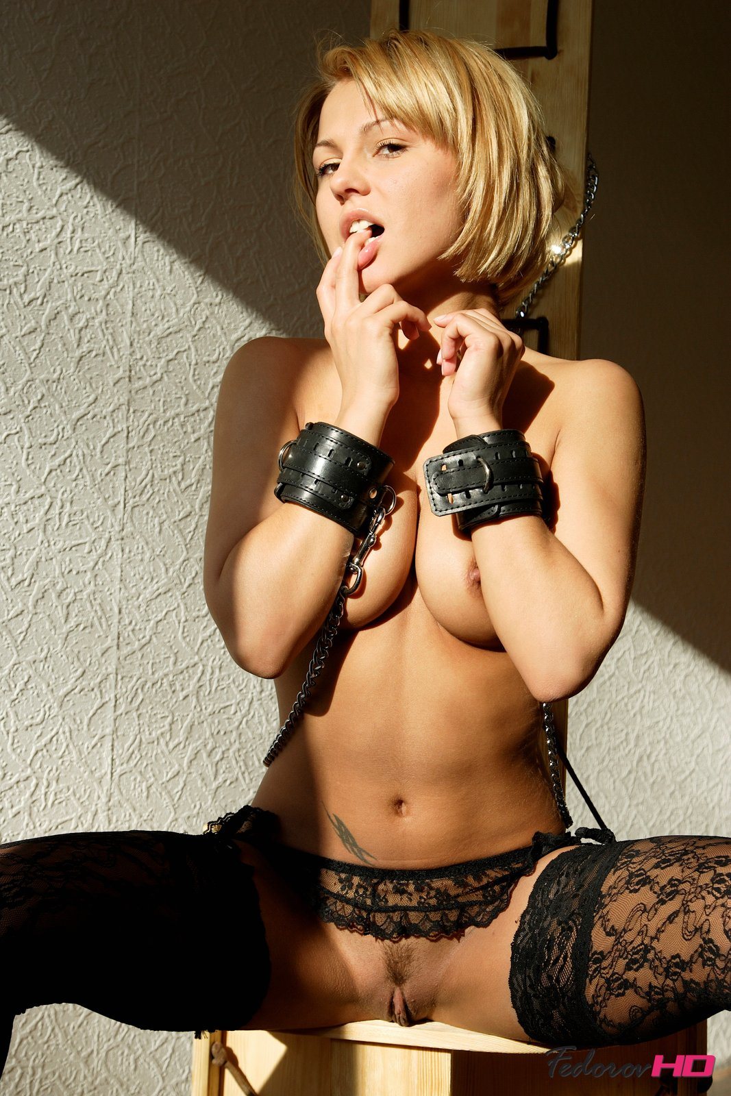 Shackles and lace stockings portrays the naughty side of this blonde, who's sexy and submissive