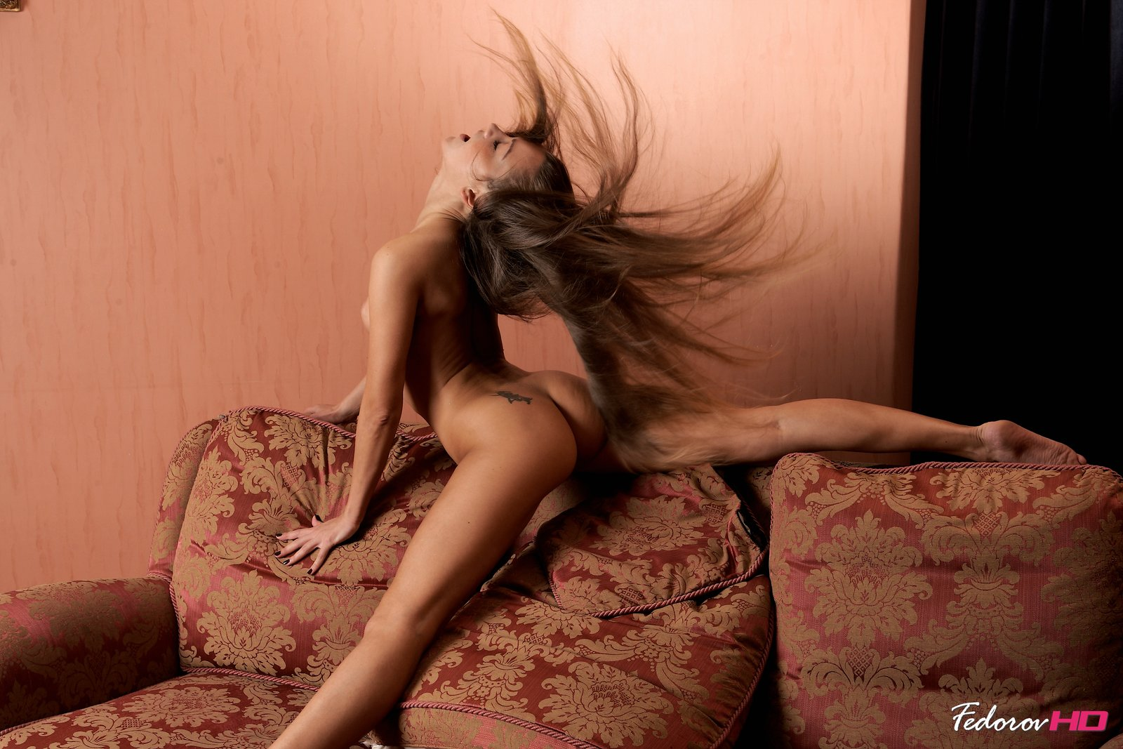 Carefree and wild, her hair flies in motion as this flexible babe stretches in a sexual manner